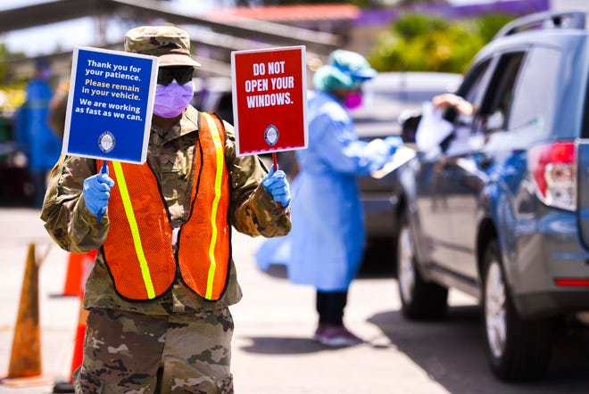 Guam National Guard member Pvt. Dennis Lomeka reminds drivers and their occupants to remain in their vehicles during COVID-19 testing near the Agat Senior Center in this May file photo.
