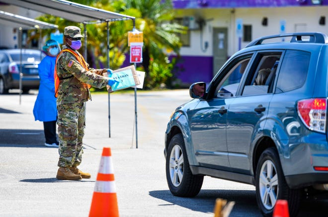 A Guam National Guard member directs a driver to an open test station during a drive-through/walk-in community testing for the coronavirus conducted by Department of Public Health and Social Services nurses near the Agat Senior Center in this May 1 file photo.