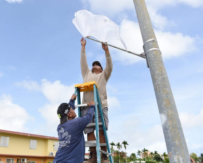 Sinajana Mayor's Office employee Alonzo Terlaje, with the assistance of fellow staff member, Tanner Manosa, sets up a moniker on a street light pole in preparation for the reconsecration of the island to the Blessed Virgin Mary in Sinajana, May 1, 2020.