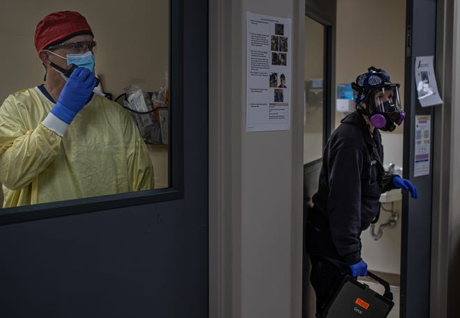 Bart Besinger, a physician in the emergency department COVID-19 room, asks a registered nurse outside the room for patient information with a communication device, a paramedic exits a self-cleaning area inside IU Health Methodist in Indianapolis on Thursday, April 30, 2020. The use of communication devices help ensure that airborne particles are not circulated outside the negative pressure rooms. Negative pressure rooms help remove harmful airborne particles.