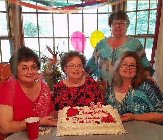 Jean Kinney Neal on her 90th birthday posing with her daughters.