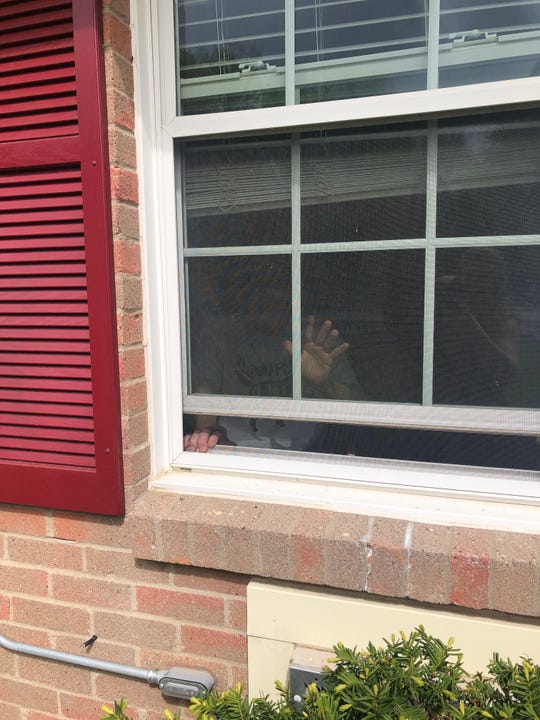 Richard Fee, 72, waves to his daughter and grandson from a window at Rivers Edge Nursing & Rehabilitation Center in Prospect, Kentucky.