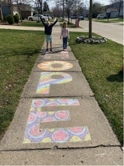Children show off their efforts to brighten up their neighborhood during the coronavirus pandemic in Michigan. This photograph was shared with the Michigan History Center as part of their work to collect images that show how the coronavirus is impacting Michiganders.