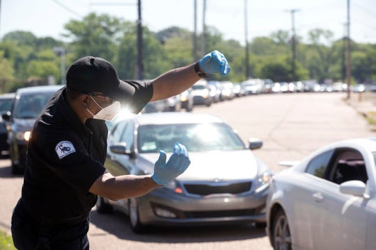 Marvin Stepter directs traffic for the Women's Foundation for a Greater Memphis as they work with volunteers to help distribute food, sanitizer and supplies to hundreds of families in need in South City on Friday, May 1, 2020.