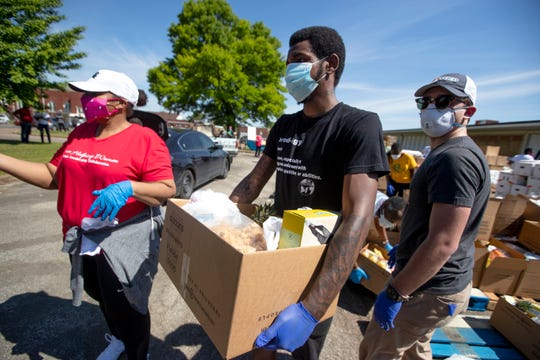Stephen Means volunteers with the Women's Foundation for a Greater Memphis to help distribute food, sanitizer and supplies to hundreds of families in need in South City on Friday, May 1, 2020.