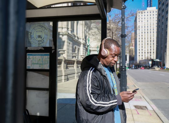 Derrick Shepherd waits for his bus at West Wisconsin Avenue and North 9th Street. The Milwaukee County Transit System has limited the number of passengers on buses to 10.