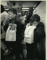 Sean Harper, 6, and his brother, Brett, 4, left George Webb restaurant in Shorewood with their historic hamburgers safely bagged in 1987 after the Brewers won 12 straight games. A crowd squeezed around the counter and along the wall waiting for their burgers.
