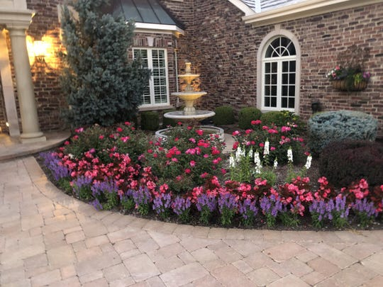 A garden bed, sometimes with some artwork, is a beautiful addition to the front of a house.
