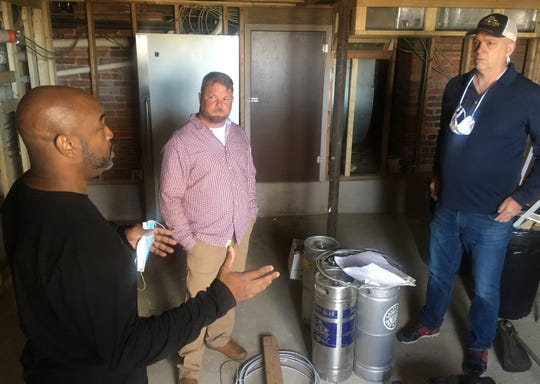 Trent Edwards, left, senior Vice President for military and community development at the Montgomery Area Chamber of Commerce, speaks with Cameron Brown of Cameron & Sons Builders and James Weddle, right, owner of Goat Haus Biergarten on Thursday, April 30, 2020, in the basement where Weddle plans to brew beer.