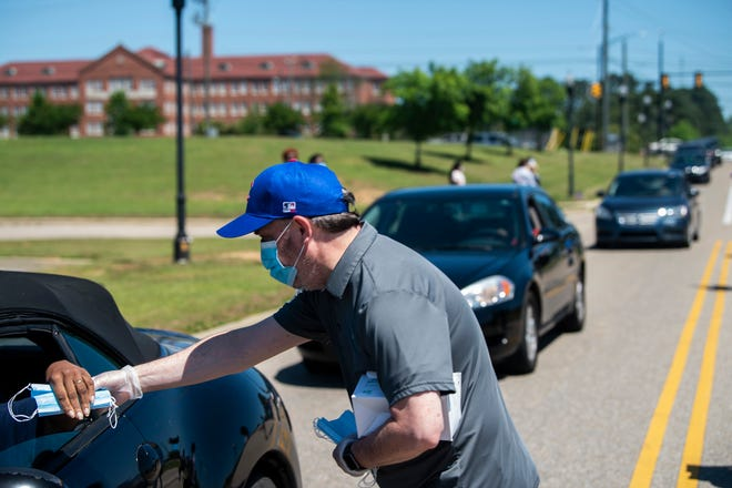 Volunteers hand out face masks and information sheets at Carver High School in Montgomery in this file photo from May.