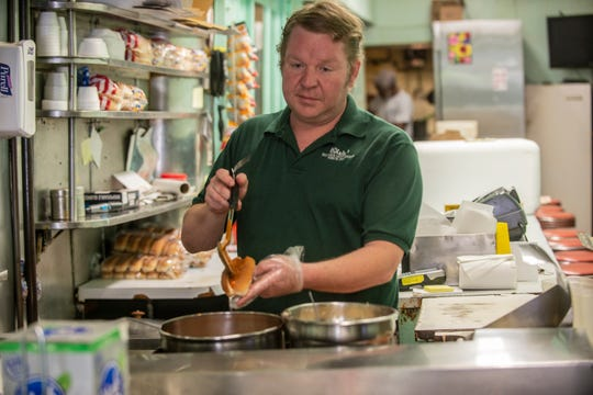 Chris' Hot Dogs owner Gus Katechis, grandson of founder Christopher Katechis at the 103-year-old restaurant, prepares to-go orders on Thursday, April 30, 2020.