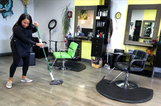 "Irene Washington, the shop manager at Salon Envy in Murfreesboro, cleans up the shop, on Thursday, April 30, 2020, as she readies the business for reopening. When asked what she thought about going back to work since the COVID-19 shutdown Washington said she was ""excited and nervous at the same time because I know that the coronavirus is very serious. Our hope is that our customers take it seriously and that they come in here with the intention to be safe."""