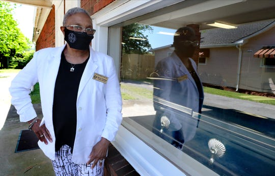 """Mary """"Kat"""" Newman, a funeral director at Hellum funeral home, in Murfreesboro, stands next to the window where family members and friends can drive by to view loved ones on Friday, May 1, 2020."""
