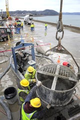 U.S. Army Corps of Engineers workers pour concrete for a barrier wall at Wolf Creek Dam in March 2013. A yearslong $594 million repair project designed to strengthen the dam and prevent catastrophic flooding wrapped up that year.