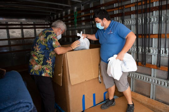 Vann R. Ellison, left, president and CEO of St. Matthew's House and St. Matthew's House employee Salvador Guzman, unload bags of donated good for the Neighborhood Health Clinic in Naples on Friday, May, 1, 2020.