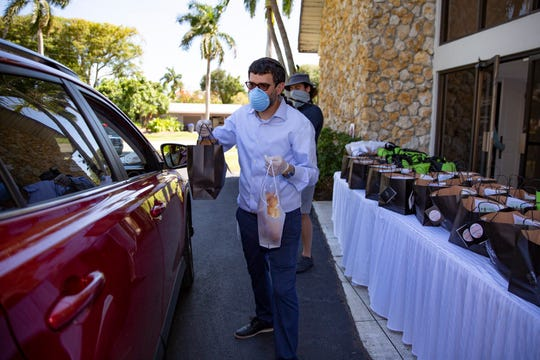Chabad of Naples Rabbi Fishel Zaklos hands out a bag containing challah and chicken soup during a pre-Shabbat Drive-By Challah and Chicken Soup event at the Chabad of Naples on Friday, May 1, 2020.