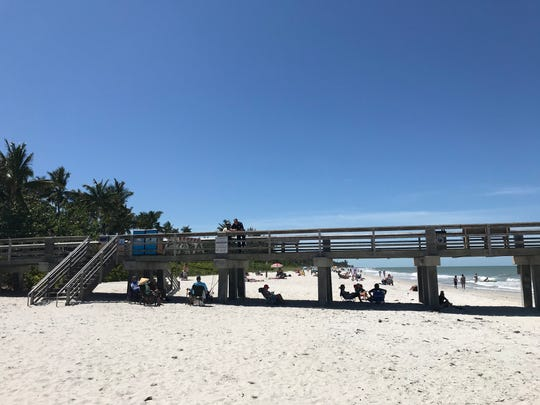 Beachgoers set up chairs underneath the Naples Pier on Friday, May 1, 2020. Beaches reopened to the public this week after closing in March due to the coronavirus.