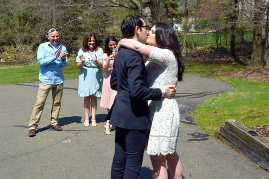 Seth and Lindsey Rubin kiss to end the brief wedding ceremony in Wayne on April 19, as the bride's family looks on.