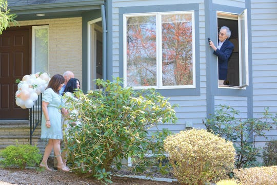 The bride's parents, Julie and Stephen Calabro, lead her down a walking path at the ceremony, while her grandfather, Martin Rudzin, leans out of a window to take a photo with his cellphone.