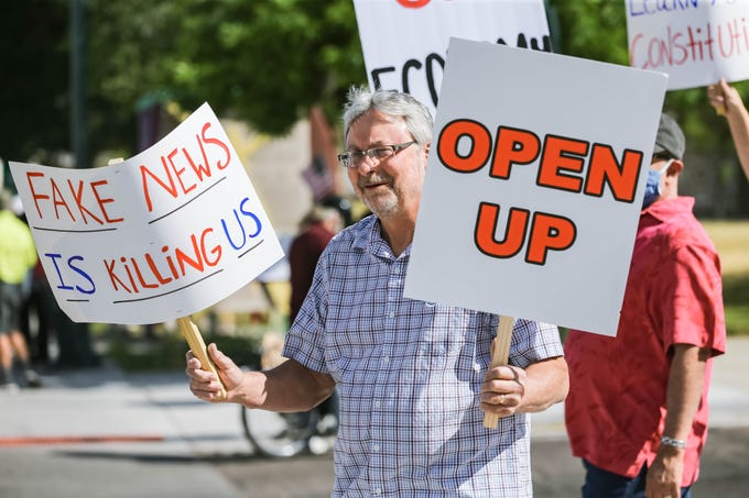 "David McDaniel holds signs that read ""Open up"" and ""Fake news is killing us"" as protesters gather at the Las Cruces City Hall building in Downtown Las Cruces on Friday, May 1, 2020."