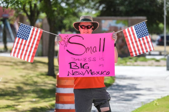 """Jeff Howey hold a sign that reads """"Open now small business is big in New Mexico"""" as protesters gather at the Las Cruces City Hall building in Downtown Las Cruces on Friday, May 1, 2020."""
