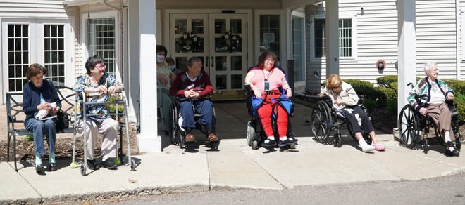 Some residents at Westland's American House gather outside on May 1, 2020 to wish their 94 year-old friend and fellow resident Jim Miles a happy birthday.