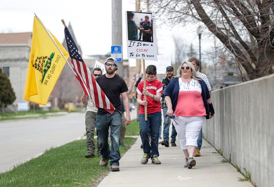 """A group of """"concerned citizens"""" protested Friday, May 1, 2020 around the Oshkosh Police Department building in Oshkosh, Wis. The group was unhappy with Wisconsin Governor Tony Evers safer at home policy which keeps many businesses in the state closed. They also were protesting the Oshkosh Police Department's actions enforcing the laws regarding businesses opening up against the policy. Doug Raflik/USA Today NETWORK-Wisconsin"""