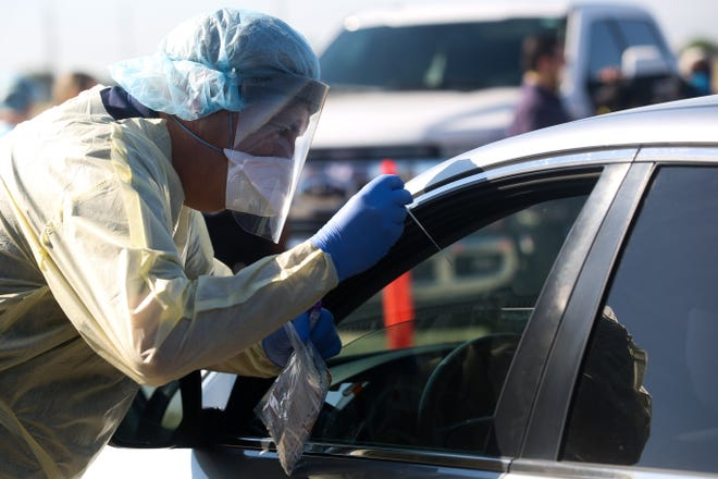 A health care worker conducts LabCorp PCR COVID-19 testing off of Dillon Rd. in Coachella, Calif. on Friday, May 1, 2020.