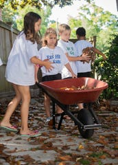 Members of the East Hill Gang clean-up a yard full of Magnolia leaves on Thursday, April 30, 2020. The group of kids have banded together and started doing chores for other people in the neighborhood during the COVID-19 shutdown.