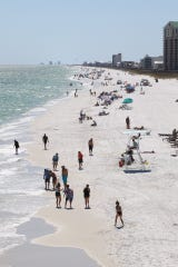 People enjoy the sun at Navarre Beach on Friday after the Santa Rosa County beach reopened after closing due to the coronavirus pandemic.