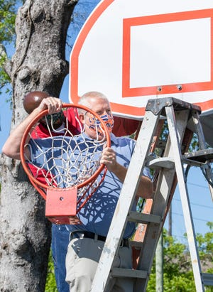 Parks superintendent Bill KImball replaces a basketball goal at Corinne Jones Community Park as city parks reopen after the coronavirus shutdown in Pensacola on Friday, May 1, 2020.