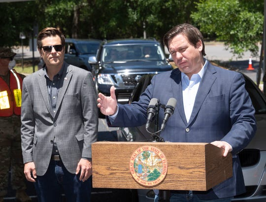 """Governor Ron DeSantis holds a press conference at the University of West Florida to discuss the lifting of his """"Stay at Home"""" order on Friday, May 1, 2020, while Congressman Matt Gaetz looks on."""