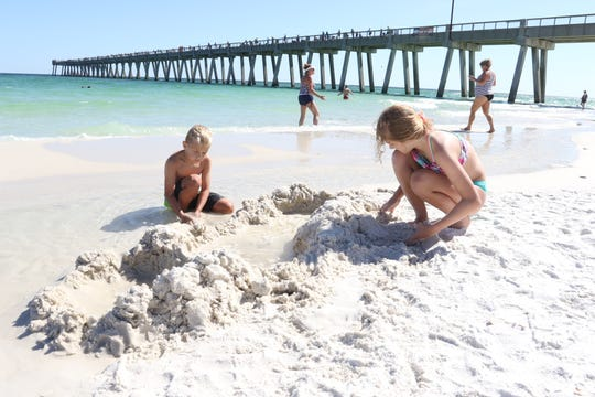Jack Ryan, 7, left, and Savannah Ryan, 11, play in the sand at Navarre Beach as the Santa Rosa County beaches reopen after the coronavirus shutdown in Navarre on Friday, May 1, 2020.