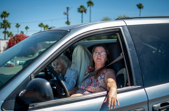 Anne-Marie Magao, an in-home caregiver for 85-year-old Gladys Daniel, left, express their disagreement with protestors gathering against Gov. Ducey's delay to reopen some businesses on May 1, 2020 in Apache Junction. Magao and Daniel drove through the area for the spectacle of the protest.