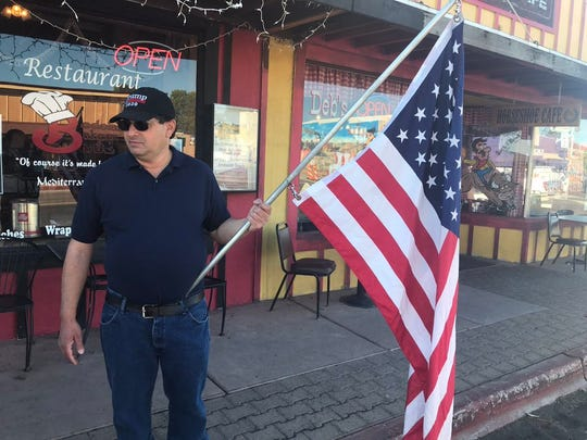 Nohl Rosen, with Patriots of Wickenburg, stands outside of Bedoian's Bakery and Bistro holding an American flag on May 1, 2020. He says he doesn't believe Gov. Ducey realizes the impact that his orders have had on smaller towns like his.