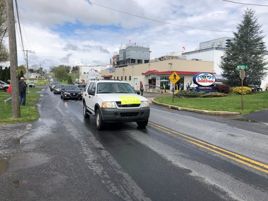 A procession of cars drove by Bell & Evans chicken plant in Fredericksburg, Pennsylvania, Friday morning demanding the plant shut down after an employee died from the coronavirus and the husband of another employee died as well.