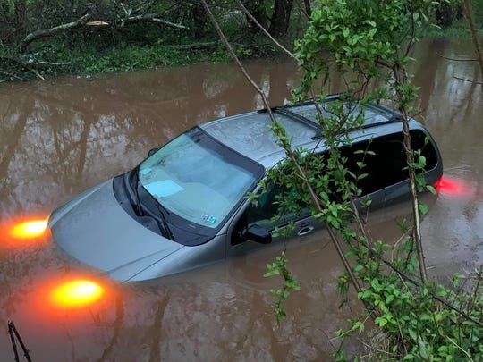 Two Northeastern Regional Police officers rescued a mother and her two toddlers after her vehicle sank in flood waters.