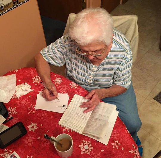 Grandma writes letters out of an old address book.