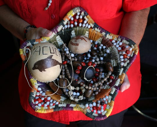 Tia Flores shows off some crafts from the Ayacucho village in Peru while in her home studio in south Reno on May 1, 2020.