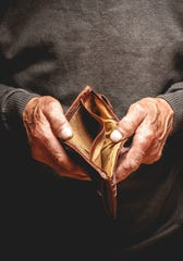 A man holds an empty wallet. (Stock photo)