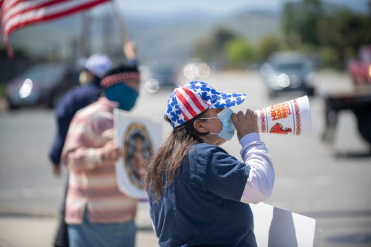 Marcela Salaic, 66, rallies with her husband and other Monterey County residents at the corner of Blanco Road and S. Main Street to protest about the Shelter-in-Place order in California on Friday, May 1, 2020.