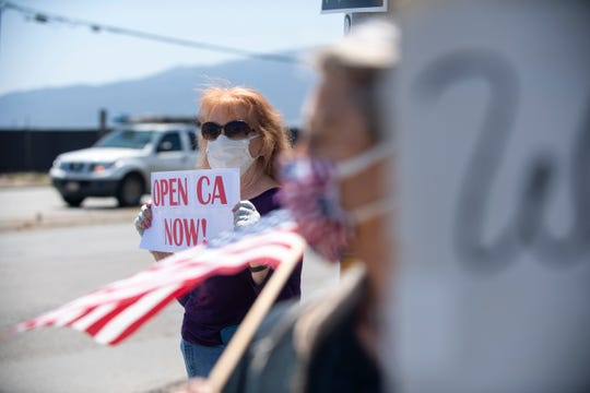 """A woman holds a sing that reads """"Open CA Now!"""" during the freedom rally in Salinas on Friday, May 1, 2020."""