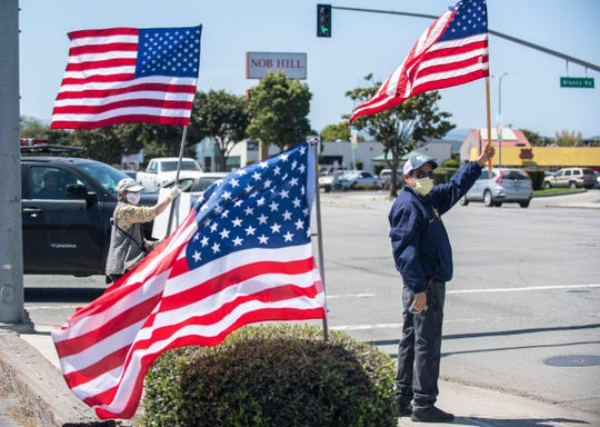 Manuel Garcia, 48, holds an American flag as he stands at the intersection of Blanco Road and S. Main Street looking at cars pass by on Friday, May 1, 2020. Garcia wants the churches to reopen as his faith is essential to him, he said.