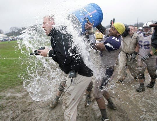 Sioux Falls head coach Kalen DeBoer is dunked on the sidelines by quarterback Lorenzo Brown (10) during the the closing moments of the NAIA National Championship football game against Carrol college, Saturday Dec. 20, 2008, 2008, in Rome, Ga. Sioux Falls won 23-7. (AP Photo/John Amis)