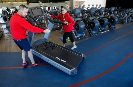Halston Adams, left, executive director at the Pat Jones YMCA, and Jamie Kidder, senior membership director, move exercise equipment in the gym on Thursday. Adams and Kidder have had to take on many different roles since the coronavirus caused the YMCA to furlough much of its staff.