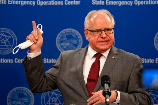 Minnesota Gov. Tim Walz answers questions while holding his mask at a news conference inside the Department of Public Safety in St. Paul on Thursday, April 30, 2020.