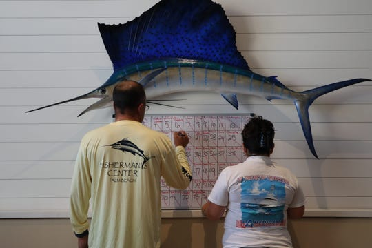 Cody and Brooke Holcomb of Vero Beach organize the board used to keep track of which anglers have bought chances to win a fishing trip aboard a charter boat for Save the Charter Boats' Facebook page.