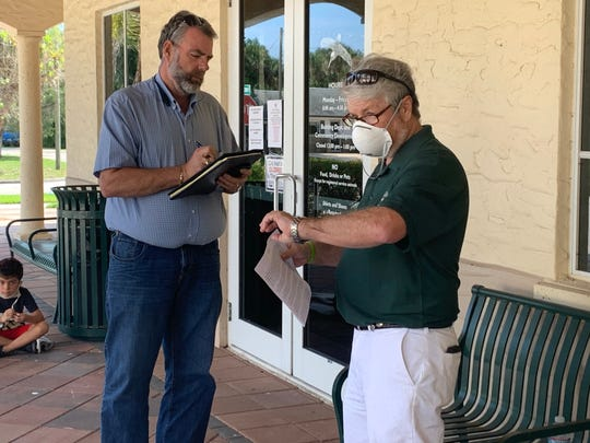 City Councilman Damien Gilliams, right, looks at his watch outside Sebastian City Hall Thursday, April 23, 2020, as Ed Arens, an investigator for State Attorney Bruce Colton, writes down information. Gilliams later was heckled by protesters as he attempted to hold a press conference.