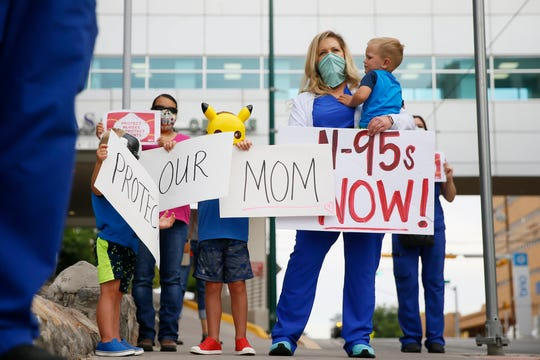Ashley Bartholomew, a registered nurse at Las Palmas Medical Center, and her three sons protest the lack of personal protective equipment, or PPE, for nurses Friday, May 1, 2020, in El Paso. The protest took place as Texas Gov. Greg Abbott loosened restrictions on businesses, allowing retail stores, shopping malls, movie theaters and restaurants to reopen at 25% capacity.