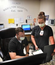 Olney Hamilton Hospital ER director Colter Garrett, RN and Samantha Isbell, MSN, look over a patient's case. Olney, Texas has seen four positive cases and one death from COVID-19 at this time.